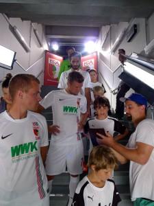 Regisseur Wolf Ehrhardt gibt neuen Text vor. Marinus mit Daniel Baier und Halil Altintop (beide FC Augsburg). beim Sky-Dreh in der WWK-Arena Augsburg, Sommer 2015